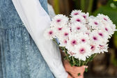 Blonde woman holding bunch of flowers — Stock Photo