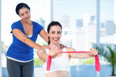 Brunette stretching with coach and pink cloth — Stock Photo