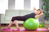 Fit woman doing sit ups on exercise ball — Stock Photo