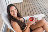 Beautiful woman relaxing and holding drink — Stock Photo