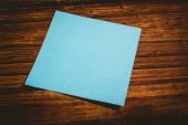 Blue post it on wooden background — Stock Photo