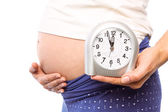 Pregnant woman showing clock and bump — Stock Photo