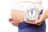 Gravid kvinna visar klocka och bula — Stockfoto