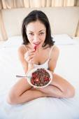 Brunette eating strawberry on bed — Stock Photo