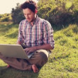 Young man using laptop in the countryside — Stock Video #73497707
