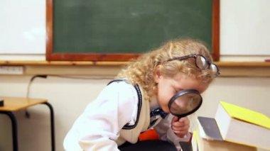 Blonde pupil using magnifying glass — Стоковое видео