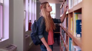 Pretty blonde student taking book from shelf — Stock Video