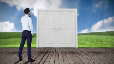 Door opening to green meadow watched by businessman — Stock Video