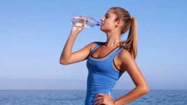 Fit woman drinking water on the beach — Stock Video