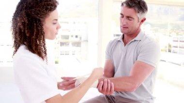Doctor bandaging her patient hand — Stock Video