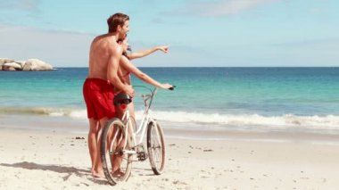 Carefree couple going on a bike ride on the beach — Stock Video