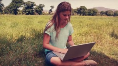 Pretty blonde relaxing in the park with her laptop — Stock Video