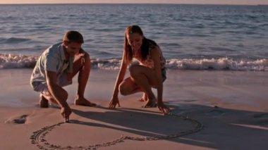 Szczęśliwa para rysunek serce w piasku — Wideo stockowe