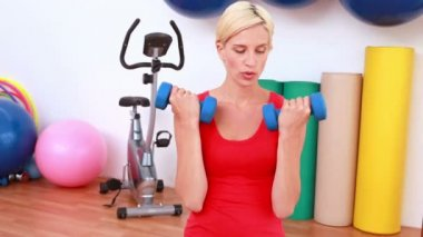 Blonde woman lifting dumbbells on exercise ball — Stock Video