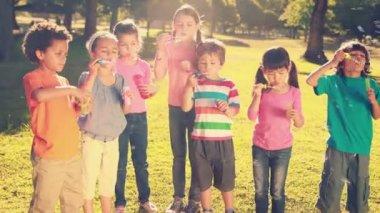 Little friends blowing bubbles in park — Stock Video