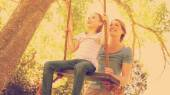 Happy mother swinging daughter at the park — Foto Stock