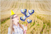 Geeky hipster holding red balloons — Stock Photo