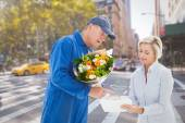 Composite image of happy flower delivery man with customer — Stock Photo