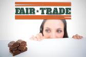 Composite image of pretty brunette peeking at chocolate — Stock Photo