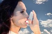 Asthmatic brunette using her inhaler — Stock Photo