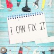 I can fix it against tools and notepad on wooden background — Stock Photo #76155233