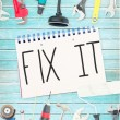 Fix it against tools and notepad on wooden background — Stock Photo #76158305