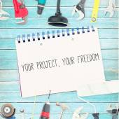 Your project, your freedom against tools and notepad on wooden b — Stock Photo