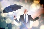 Businessman sheltering under black umbrella — Stock Photo