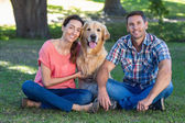 Couple with their dog in park — Stock Photo