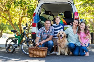 Family with dog getting ready for road trip