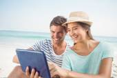 Couple using tablet at beach — Stock Photo