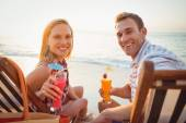 Couple drinking cocktails at beach — Stock Photo