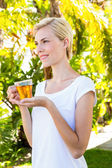 Blonde woman holding glass of tea — Stock Photo