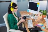 Brunette holding digital camera and listening music — Stock Photo