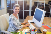 Smiling businesswoman typing on keyboard — Stock Photo