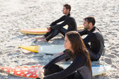 Friends on wetsuits with surfboard at beach — Stock Photo