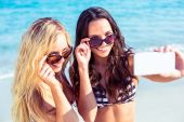 Friends in swimsuits taking selfie at beach — Stock fotografie