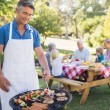 Man doing barbecue for his family — Stock Photo #76337511