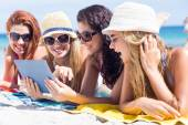 Happy friends wearing sun glasses and using tablet — Stock Photo