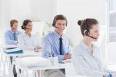 Equipe de negócios trabalhando em computadores e usando fones de ouvido — Fotografia Stock