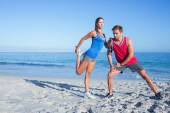 Happy couple stretching together beside the water — Stock Photo