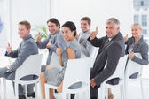 Smiling business team looking at camera during conference — Stock Photo