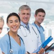 Team of smiling doctors looking at camera — Stock Photo #76342673