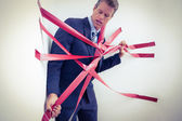 Businessman trapped by red tape — Stock Photo