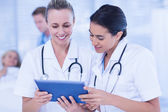 Doctors looking at clipboard while theirs colleagues speaks with — Stock Photo
