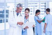 Mannelijke en vrouwelijke artsen die werkzaam zijn op rapporten — Stockfoto
