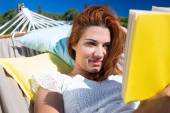 Brunette reading a book while relaxing in the hammock — Stock Photo