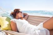 Brunette relaxing in the hammock with sunglasses — Stock Photo