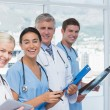 Team of smiling doctors looking at camera — Stock Photo #76350569