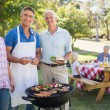 Man doing barbecue for family — Stock Photo #76351743